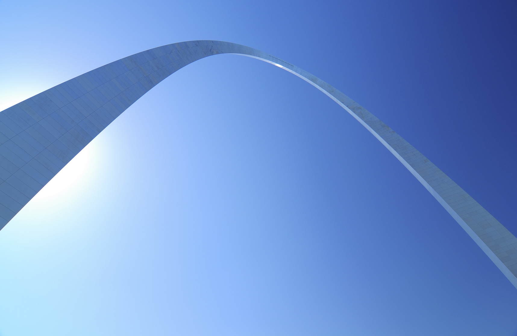A dramatic wide angle view of the Gateway Arch in Saint Louis, with the arch backlit against the sun.